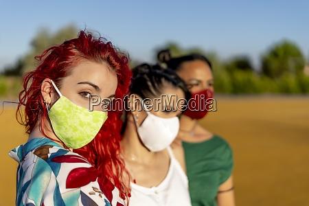 freunde tragen schuetzende gesichtsmaske waehrend sie