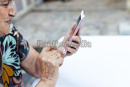 nahaufnahme der seniorin mit smartphone am