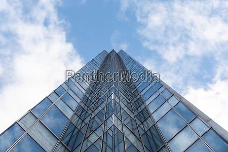 grosser moderner bueroglas hochhaus gegen blauen