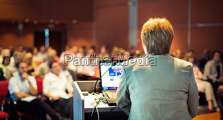 geschaeftsfrau die auf der konferenz referiert