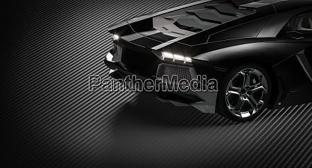 detail eines schwarzen supersportwagens auf kohlefaserhintergrund