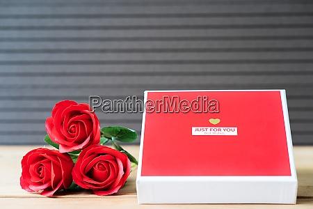rote rosen und herzfoermige kiste auf