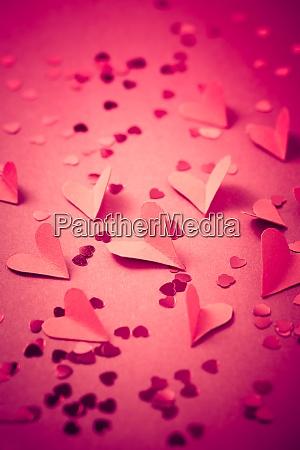 rote papierherzen auf rotem hintergrund als