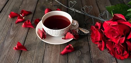 tasse tee mit roten rosen