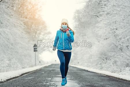 frau laeuft oder joggt mit gesichtsmaske