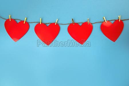vier rote herzen haengen an schnur