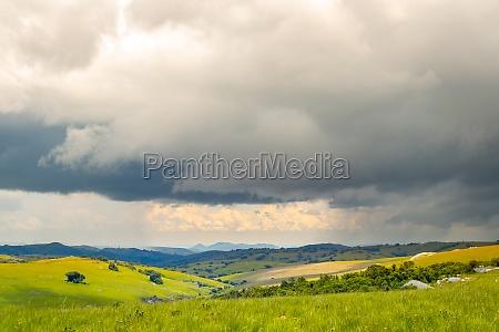 dramatische landschaft sanfte huegel unter gewitterwolken