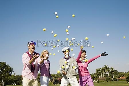 vier freunde werfen golfbaelle in midair