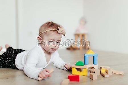 kleines kind spielt mit bunten holzbausteinen