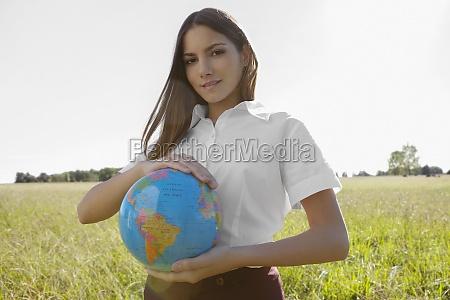 portraet eines teenagers der einen globus