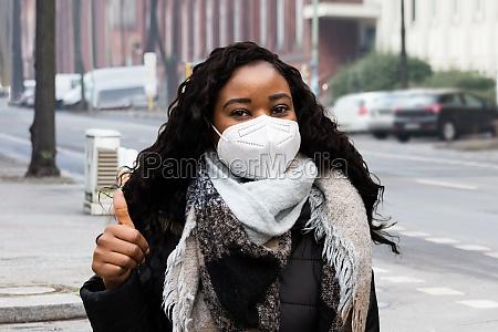 afroamerikanische frau traegt medizinische gesichtsmaske