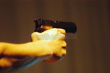 person die mit einer pistole zielt