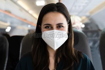 frau in gesichtsmaske auf flugzeug