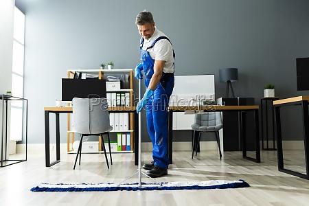 maennliche janitor mopping boden in gesichtsmaske