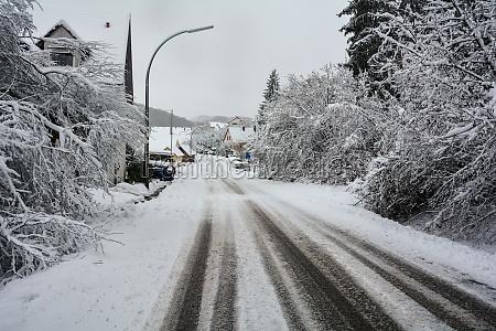 landstrasse mit viel schnee zum dorf