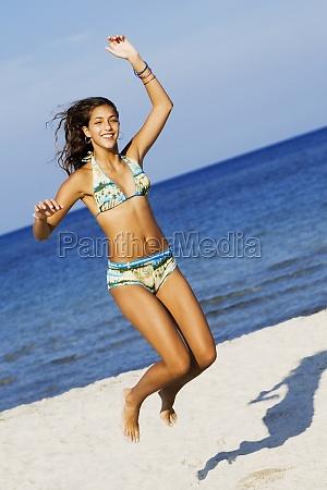 teenage maedchen springen auf dem strand