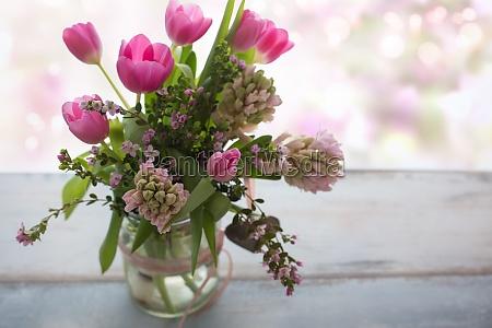 komposition mit frischen fruehlingsblumen auf grauem