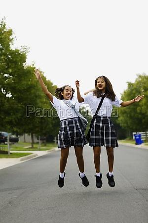 zwei schuelerinnen springen auf die strasse