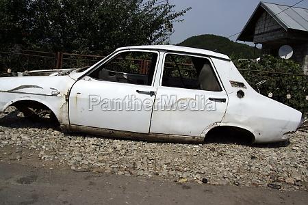 weisses rostiges auto vor dem verschrotten