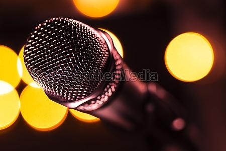 nahaufnahme von mikrofon und buehnenleuchten