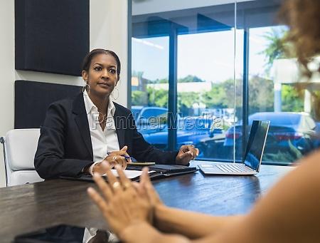 zwei geschaeftsfrauen sprechen am konferenztisch