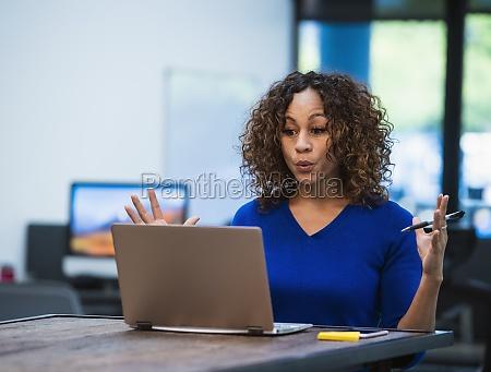 frau schaut auf laptop am schreibtisch