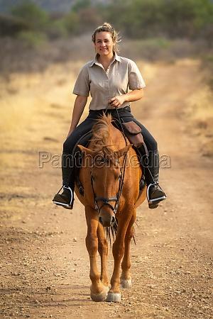 laechelnde blondine reitet pferd auf feldweg