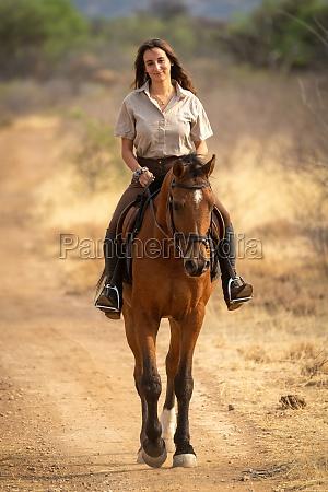 laechelnde bruenette reitet pferd auf feldweg