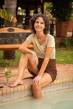 laechelnde bruenette sitzt mit cocktail am