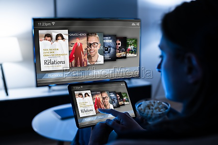 frau schaut fernsehen ueber tablet fernsehen