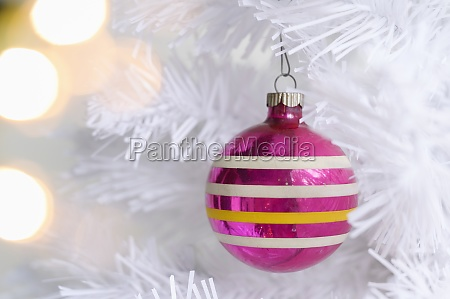 rosa ornament auf weissen weihnachtsbaum