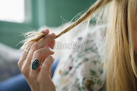 frau beruehrt ihre haare nahaufnahme