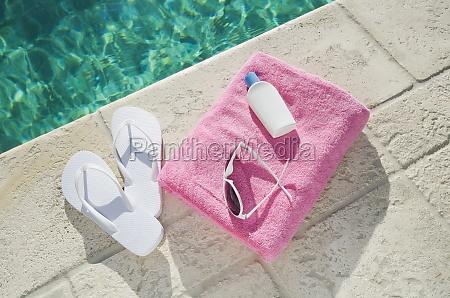 sandalen und handtuch am pool