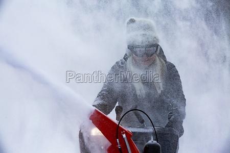 seniorin raeumt schnee mit schneefraese