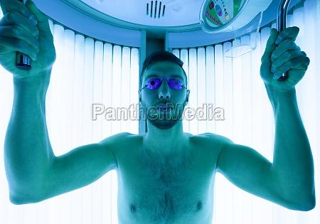 junger mann im solarium im schoenheitssalon
