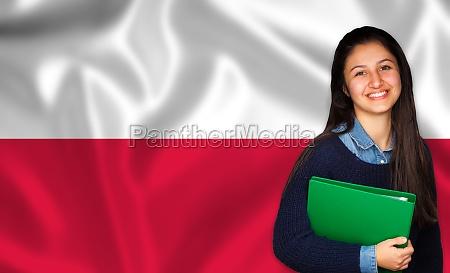 teenager student laechelt ueber polnische flagge