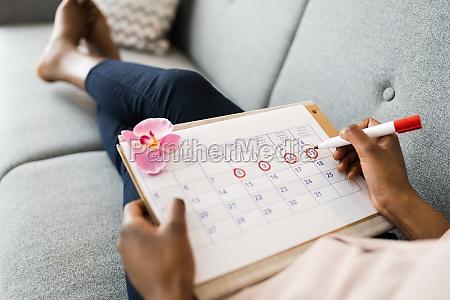 afrikanische frau mit menstruationszyklus kalender