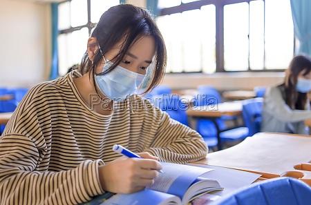 jugendliche schueler tragen schutzmasken und studieren