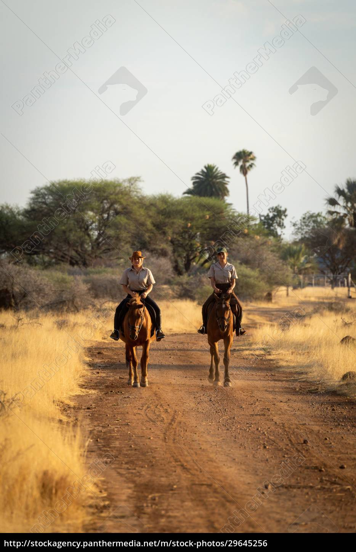 two, horsewomen, ride, side-by-side, on, dirt - 29645256