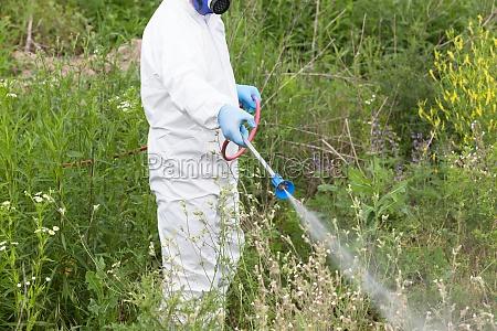 arbeiter in schutzarbeitskleidung sprueht herbizid auf
