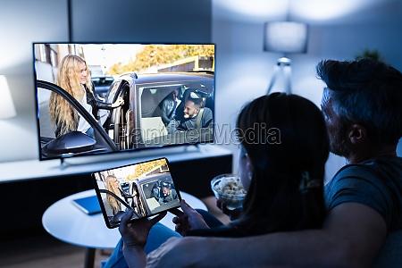 familie schaut fernsehen ueber tablet fernsehen