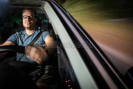 huebscher junger fahrer faehrt sein auto