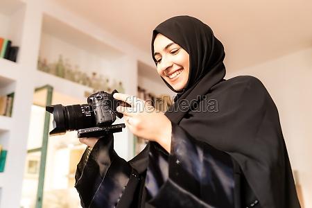 junge muslimische frau mit kamera laechelnd