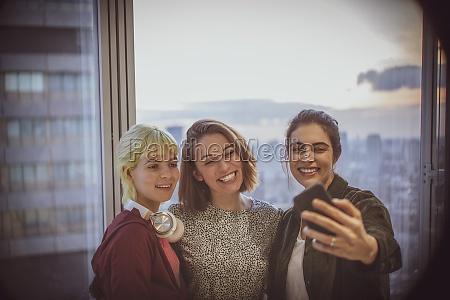 laechelnde geschaeftsfrauen beim selfie am buerofenster