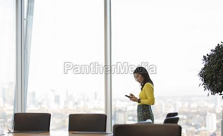 geschaeftsfrau mit smartphone im hochhaus konferenzraum
