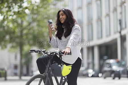 frau auf fahrrad mit smartphone auf