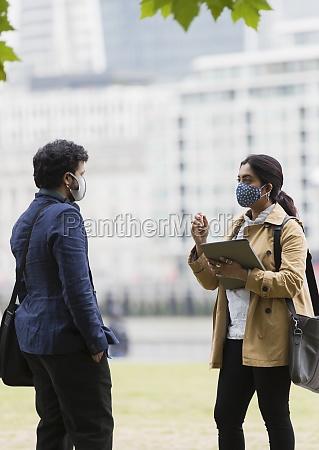 geschaeftsleute in gesichtsmasken sprechen im stadtpark