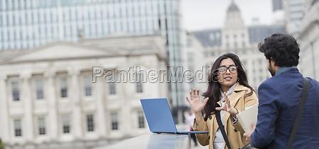 geschaeftsleute mit laptop auf stadtbruecke