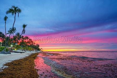 sonnenuntergang ueber tropischem strand