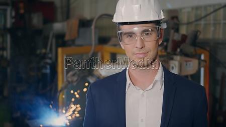 geschaeftsmann in anzuegen sicherheitshuete brille laecheln